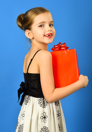 gift box with bow in the childrens hands on blue background