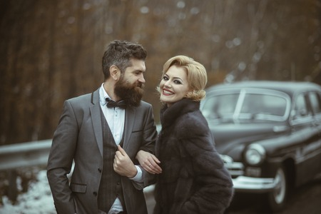 retro car in forest and winter time with happy couple in love