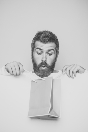 Mens heals care. man with long beard on surprised face with shopping bag