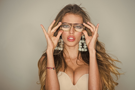 Woman face beauty. Woman with big breasts wears old fashioned eyeglasses for vision. Optics shop concept. Sexy nude girl with makeup, long hair, light background. Girl short sightedness needs modern eyeglasses Stockfoto