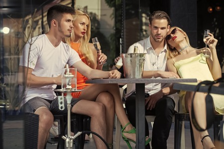 Woman face beauty. twins women and men relax in shisha cafe outdoor Stock Photo