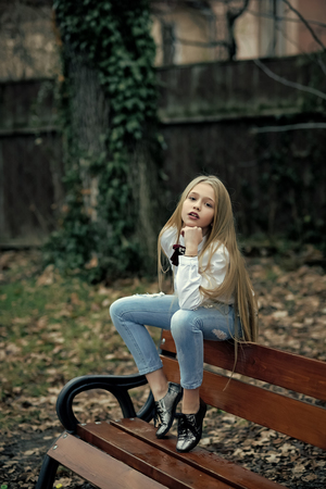 Girl in fashionable jeans sit on bench, fashion. Small child with long blond hair, hairstyle outdoor beauty. Baby beauty, hair and look. Childhood and youth hair care. Kid fashion trend and style. Child Childhood Children Happiness Concept. Foto de archivo