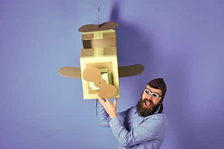 Man with serious emotion. father on blue background with cardboard plane