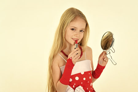 childhood and happiness. childhood, little girl pit red lipstick on lips with mirror. Happy kid having fun. Stock Photo