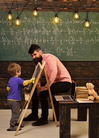Kids playing - happy game. Kids playing - happy game. Tutor explaining math to little kid. Turned back boy wiping chalkboard with yellow cloth. Daddy sitting on the table while talking to the son Banco de Imagens