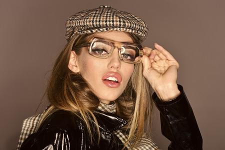 Woman on pensive face with make up wears checkered accessories and glasses for vision. Accessories concept. Girl wears kepi, scarf and glasses, grey background. Sexy lady in stylish outfit, close up Stock fotó