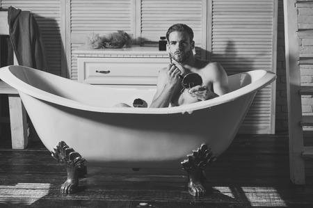 Mens heals care. Man shaving with razor blade and shaving cream Фото со стока
