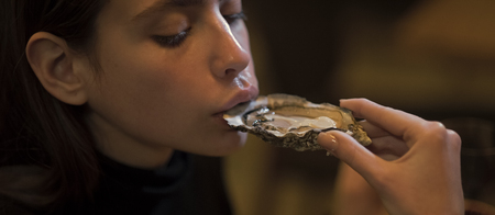 Young woman eating oyster in luxury restaurant. Face girl for magazine cover. Girl face portrait in your advertisnent.
