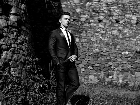 Elegant Man in Suit. Young man poses outdoor