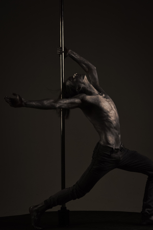 Mens heals body care. Plasticity concept. Guy, athlete, sportsman puts hand on metallic pole Standard-Bild - 102163804