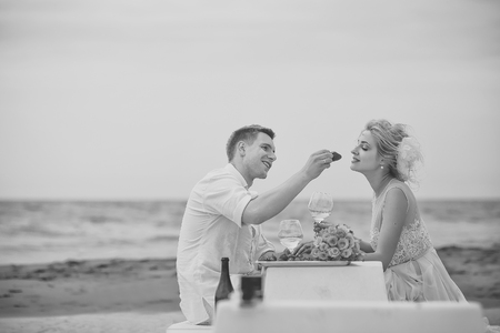 Romantic couple. Wedding couple eating on beach