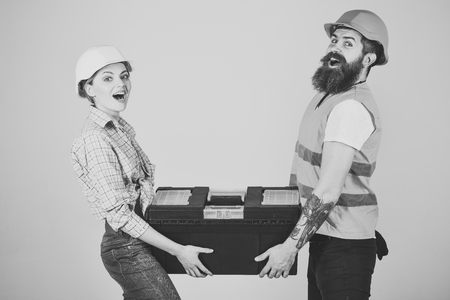 Repairman and girlfriend holding toolbox together, copy space. Smiling woman in helmet excited about renovation. Builders with toolbox, couple in love makes repair grey background. Renovation concept. Фото со стока