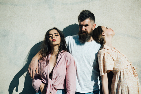Bearded man standing with two women over white wall. Man choosing between brutal femme fatale and innocent young girl, love triangle, relationship problems concept. Stock Photo