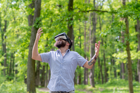 Happy bearded man using VR glasses in forest or park. Hipster with stylish beard enjoying 3D view device. Bearded man wearing virtual reality goggles looking up at sky, digital technology concept. Archivio Fotografico
