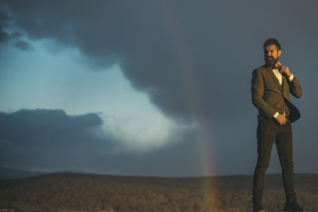 Hipster and rainbow on grey sky. Hipster in classic coat with bow tie on vacation, copy space.
