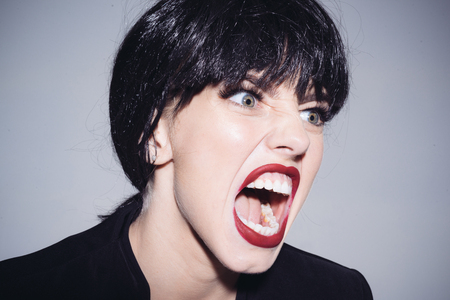 Screaming female with crazy look isolated on gray background, emotions concept. Bad tempered businesswoman in black jacket wearing dark wig expressing anger.