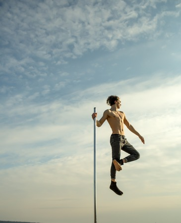 Athletic guy make acrobatic elements on pylon. Strong man dancer workout on pole. Young man dancing on pylon. Pole dance sport. Sexy macho man fly on blue sky background. In good shape