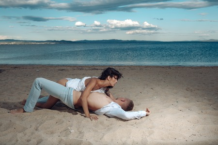Love relations of couple at sea. Summer holidays and paradise travel vacation. Couple in love with body relax on beach sand. Family and valentines day. Sexy woman and man have games