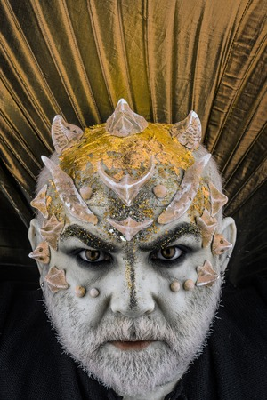 Head with thorns or warts, face covered with glitters, close up. Demon with golden collar, black background. Alien, demon, sorcerer makeup. Senior man with beard, with monster makeup. Fantasy concept.