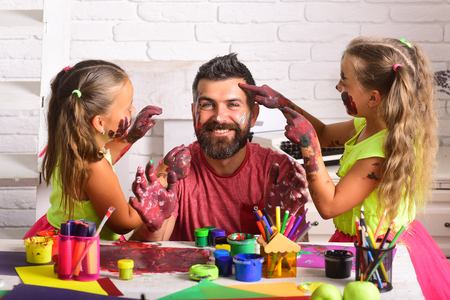 Girls drawing on man face skin with colorful paints. Daughters and dad smiling with painted hands. Fathers day and family concept. Body art and painting. Creativity and imagination.