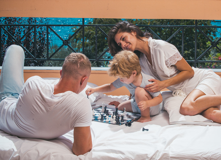 Child play chess with father and mother. child with parents play chess on summer balcony 写真素材