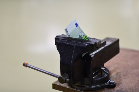 Money squeezed in vise. Money fixed by vise tool on workbench. Stock Photo