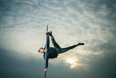 Athletic man on portable pylon in sunset sky