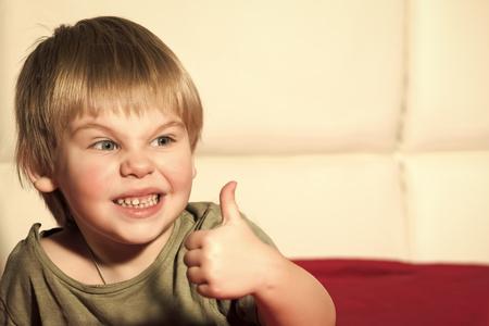 Happy kid having fun. Small boy with thumb up.