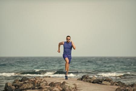 Mens heals body care. Runner man running on sea beach on blue sky