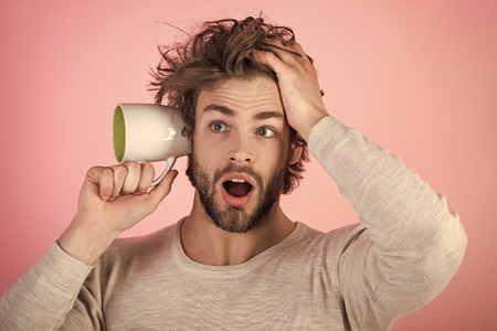 Mens heals care. surprised man with disheveled hair hold cup at ear, gossip Фото со стока