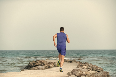 Mens heals body care. Sportsman back view training outdoors on seascape