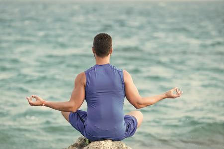 Mens heals body care. yogi having meditation at beach.