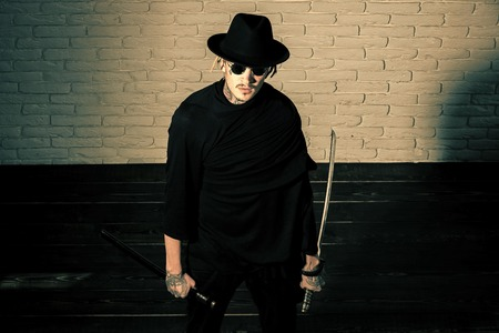 Serious man. Warrior in black sunglasses, hat and clothes, top view