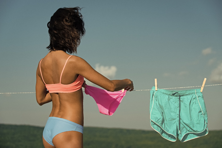 Sexy woman. girl or housewife hang underwear on clothespin and clothesline
