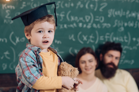 Support concept. Kid holds teddy bear and performing. Parents listening their son, chalkboard on background. Smart child in graduate cap like to perform. Boy presenting his knowledge to mom and dad. 版權商用圖片