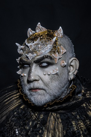 Demon with golden collar on black background. Man with thorns or warts, face covered with glitters. Senior man with white beard dressed like monster. Alien, demon, sorcerer makeup. Fantasy concept.