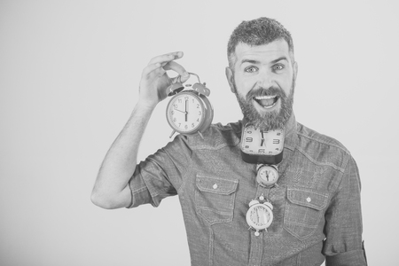 Happy man. man with beard on happy face hold many alarm clock Stock Photo
