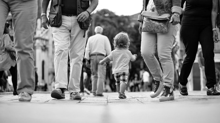 Kids playing - happy game. Baby boy walking in crowd