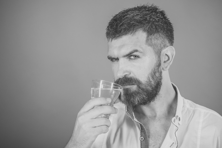 Men face skin care. Portrait Men face in your advertisnent. Man with long beard hold water glass on red background.