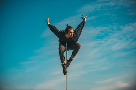 young man practicing on the pole on blue sky background.