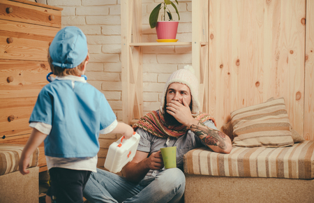 Father and son playing doctor, healthcare and treatment concept. Emergency medical specialist visiting patient at home. Man with long beard in knitted white hat coughing due to flu Foto de archivo - 102299347