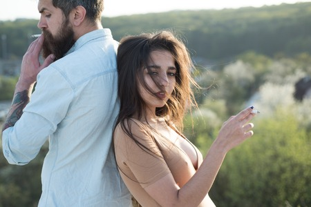 Couple on relaxed faces smoking outdoors, nature on background, defocused. Man and woman holds cigarette on spring day. Couple in love spend time outdoors and smoking. Smoking habit concept. Banco de Imagens