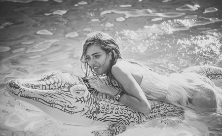 Sensual sexy woman. Sexy woman on sea with inflatable mattress. Relax in luxury swimming pool. Fashion crocodile leather and girl in water. Adventures of girl on crocodile. Summer vacation and travel to ocean, maldives