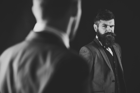 Meeting of reputable businessmen, black background. Man with beard on suspicious face, and shoulders of partner, defocused. Business meeting concept. Businessmen, business partners in formal wear Stock Photo