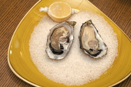 Oyster with lemon and crushed ice. healthy delicacy with omega 3 vitamin. Seafood and Mediterranean cuisine. Dieting and health. eating fresh oyster shellfish in luxury restaurant Stock Photo