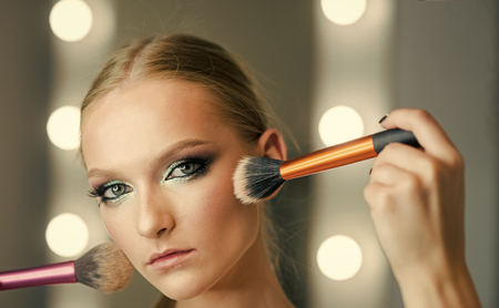 Visage model with makeup brushes. Visage course for glamour makeup. Sexy woman.