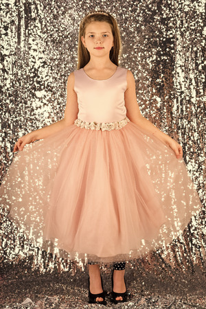 Little girl in fashionable dress, prom. Fashion model on silver background, beauty. Child girl in stylish glamour dress, elegance. Look, hairdresser, makeup. Fashion and beauty, little princess