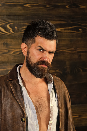 Mens heals body care. Haircut of bearded man, archaism. Haircut and trendy hipster beard of young man in leather jacke