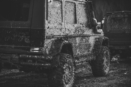 Dirty offroad cars on dark background, back view. 写真素材