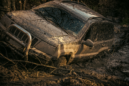 SUV covered with mud on path with deep rut. Archivio Fotografico - 102526217